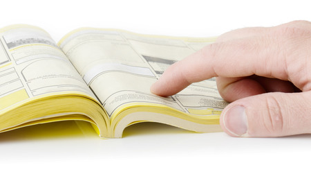 Foto de yellow pages searching with finger, blank spaces for text input. all information burred  - Imagen libre de derechos