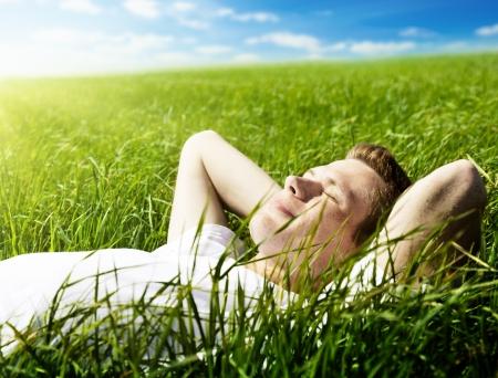 Foto de young man in spring grass - Imagen libre de derechos