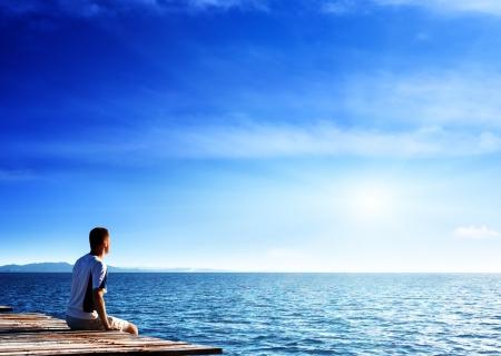 Foto de young man relax siting on pier  - Imagen libre de derechos