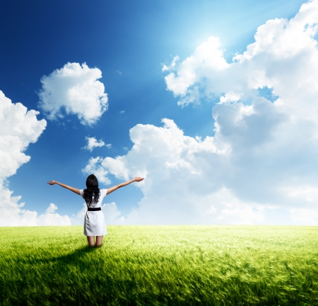 Foto de happy young woman in white dress standing in field  - Imagen libre de derechos