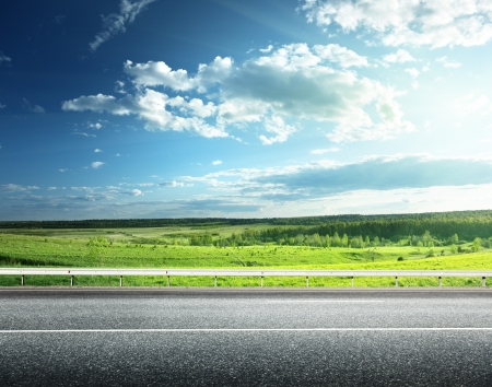 Foto de asphalt road and perfect green field - Imagen libre de derechos