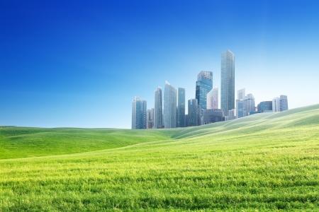 Foto de spring field and modern city  - Imagen libre de derechos
