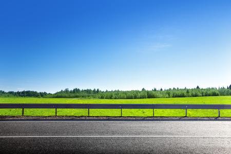 Photo pour road and field of spring grass - image libre de droit