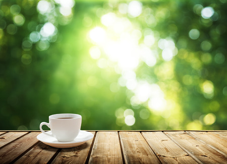 Foto de cup coffee and sunny trees background - Imagen libre de derechos