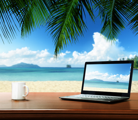 Foto de notebook on table and tropical beach - Imagen libre de derechos