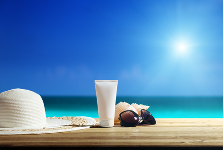 Photo for Sun lotion and sunglasses on the beach - Royalty Free Image