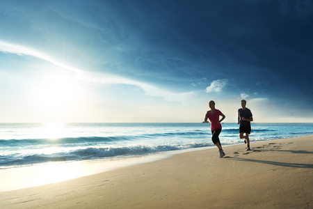 Photo pour Man and women running on tropical beach at sunset - image libre de droit