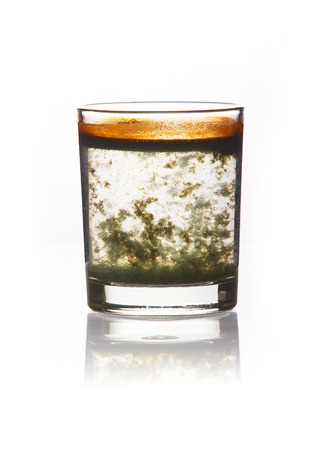 Photo pour toxic water. glass filled with dirty water with a yellow-green precipitate - image libre de droit