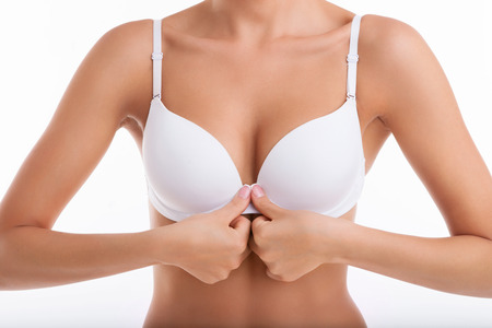Photo pour Close up of breast of fit woman unbuttoning her white bra in front of her body. Isolated on white background - image libre de droit