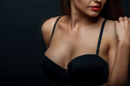 Photo pour Close up of breast of attractive woman presenting her black bra. She is touching her shoulder gently. Isolated on black background and there is copy space in left side - image libre de droit