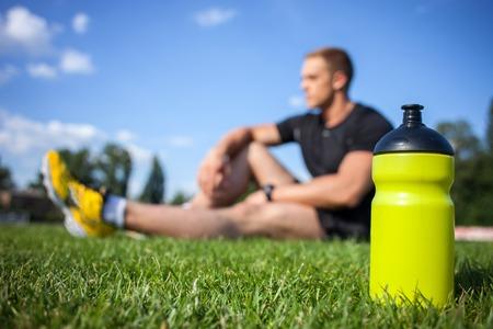 Photo pour Healthy male athlete is resting on grass. Focus on bottle of water - image libre de droit