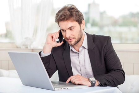 Photo pour Handsome businessman is sitting at the table in restaurant and talking on the phone. He is looking at his notebook with concentration - image libre de droit