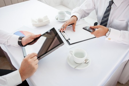 Photo for Close up of hands of two businessmen sitting at the table in restaurant. They are doing their work. One man is holding a laptop. Another businessman is writing down main ideas and holding phone - Royalty Free Image
