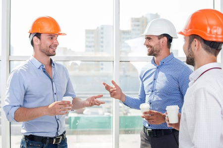 Foto de Attractive builders are drinking coffee on a break. They are talking and smiling. The men are looking at each other with trust - Imagen libre de derechos