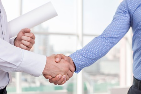 Photo pour Close up of arms of architect and foreman shaking hands. The new plan was approved. They built a consensus. The architect is holding a blueprint - image libre de droit