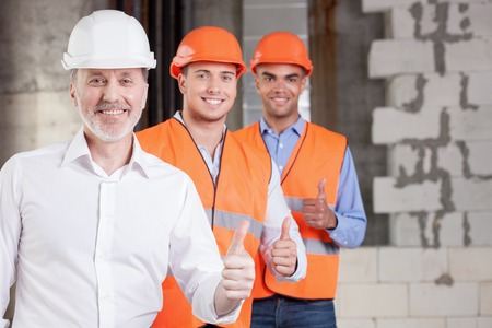 Photo for Skilled old architect and young workers are giving thumbs up. Their project was approved. The men are smiling and looking at the camera with happiness. Copy space in right side - Royalty Free Image