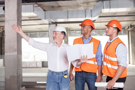 Foto de Senior architect is expressing his ideas concerning building. He is pointing his arm sideways and smiling. The man is holding a blueprint. The builders are looking aside with interest and joy - Imagen libre de derechos