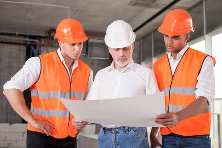 Foto de Successful old architect and two workers are discussing the plan of building. They are looking at the blueprint with seriousness - Imagen libre de derechos
