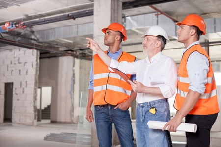 Foto per Experienced old architect is explaining to construction team the concepts of project. He is pointing his finger sideways seriously. The workers are looking there with interest. Copy space in left side - Immagine Royalty Free