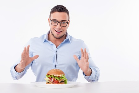 Photo pour Attractive guy is looking at the hamburger with temptation. He is ready to eat it. The guy is sitting at the table and happily smiling. Isolated on background and copy space in right side - image libre de droit