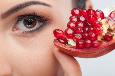Photo pour Close up of female eye. The woman is touching a slice of pomegranate to her face with enjoyment - image libre de droit