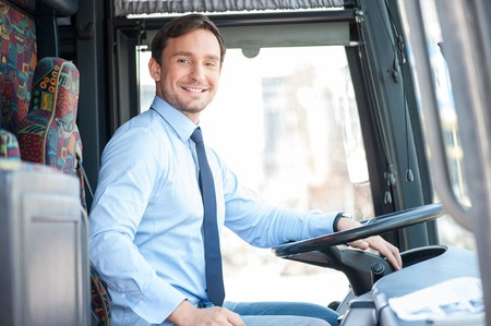 Photo pour Handsome bus driver is sitting at steering wheel. He is looking at the camera and smiling - image libre de droit