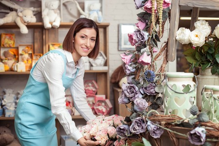 Photo pour Attractive female florist is making a bouquet with inspiration. She is standing in her workshop and smiling. The lady is looking at the camera happily - image libre de droit