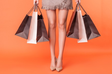 Photo pour Close up of female legs with shoes on high heels. The girl is standing and holding many packets of bought things. Isolated on orange background - image libre de droit