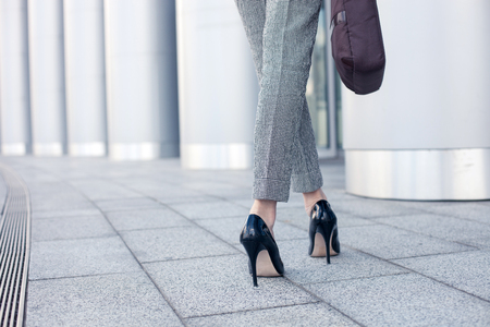 Photo pour Close up of female legs of worker standing near her office. The woman is wearing formalwear and shoes on high heels. She is holding a handbag. Copy space in left side - image libre de droit