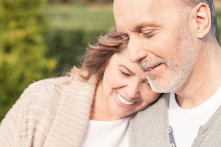 Photo for Pretty mature husband and wife are standing and embracing in park. They are smiling - Royalty Free Image