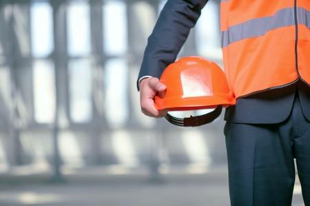 Foto de Close up of unrecognizable builder standing and holding an orange helmet in his hand. The man is wearing a workwear. Copy space in left side - Imagen libre de derechos