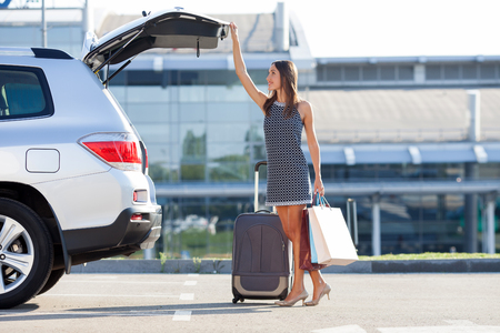 Photo pour Cheerful woman is standing near her car and closing the trunk. She is holding many packets of bought things and smiling. There is a suitcase near her. Copy space in right side - image libre de droit