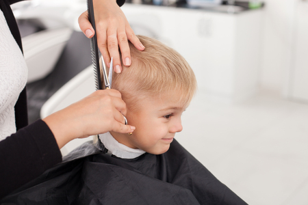Photo pour Close up of hands of hairdresser. The woman is standing and making haircut for small boy. She is holding a comb and scissors. The child is sitting and smiling - image libre de droit