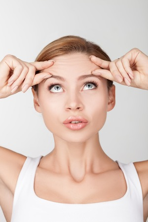 Photo pour Beautiful healthy woman is touching and wrinkling her forehead. She is looking up at wrinkles with disappointment. Isolated on background - image libre de droit