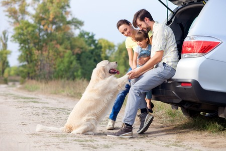 Photo pour Pretty family is resting in forest and playing with dog. They are sitting on open car boot and embracing. The man and woman with girl are smiling. Copy space in left side - image libre de droit
