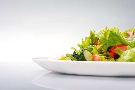 Photo pour Close up of fresh salad of lettuce, cucumber and tomato on plate Isolated on blue background - image libre de droit