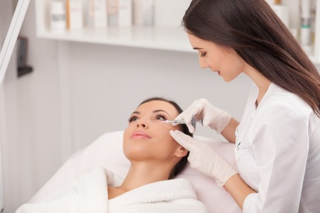 Photo pour Attractive young woman is getting a collage injection in her face. The expert beautician is filling female nasolabial wrinkles by hyaluronic acid and smiling - image libre de droit