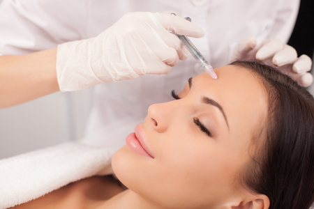 Photo pour Close up of hands of expert beautician injecting botox in female forehead. - image libre de droit