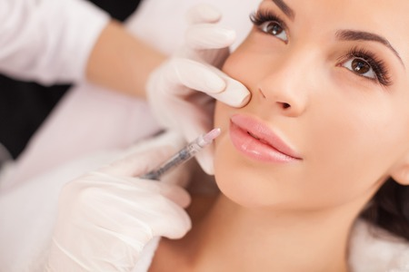 Foto de Close up of hands of cosmetologist making botox injection in female lips. The young beautiful woman is receiving procedure with enjoyment - Imagen libre de derechos