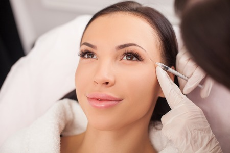 Photo pour Beautiful young woman is getting botox injection at clinic. The doctor is holding syringe near her eyebrows carefully - image libre de droit
