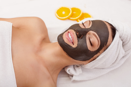 Photo pour Beautiful young woman is getting facial chocolate mask at spa - image libre de droit