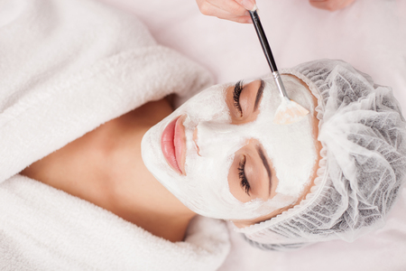 Photo pour Beautiful young woman is getting facial mask at spa. She is lying and relaxing. Her eyes are closed with pleasure. The cosmetologist is applying cream on her face with brush - image libre de droit