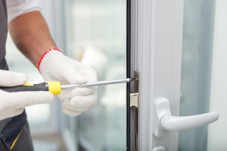 Foto de Close up of hands of young carpenter holding a screwdriver and fixing the lock of door. The man is standing in workwear - Imagen libre de derechos