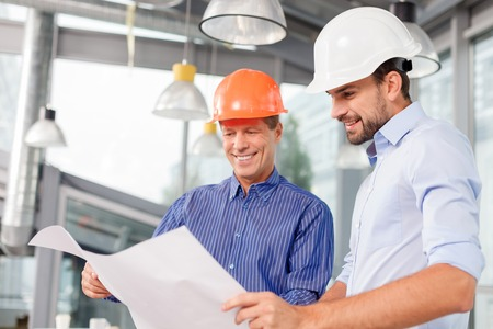 Photo pour Professional two engineers are planning the construction. They are holding a blueprint and looking at it with inspiration. The men are standing and smiling - image libre de droit