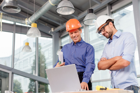 Photo for Professional two engineers are discussing the new project. They are using a laptop and smiling. The senior man is standing and holding the blueprint. Copy space in left side - Royalty Free Image