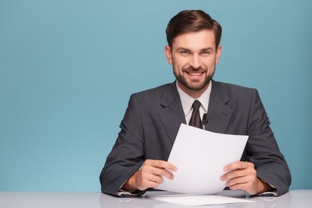 Foto de Attractive young tv newscaster is reporting news. He is sitting at the desk in a studio. The man is looking at camera and smiling. Isolated on blue background and copy space in left side - Imagen libre de derechos