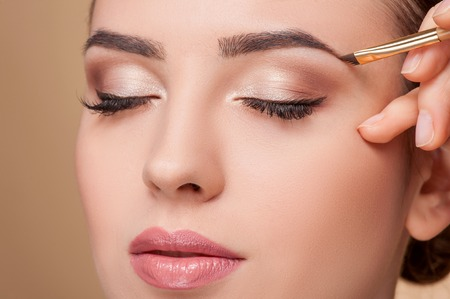 Foto de Close up of beautiful face of young woman getting make-up. The artist is applying eyeshadow on her eyebrow with brush. The lady closed eyes with relaxation - Imagen libre de derechos