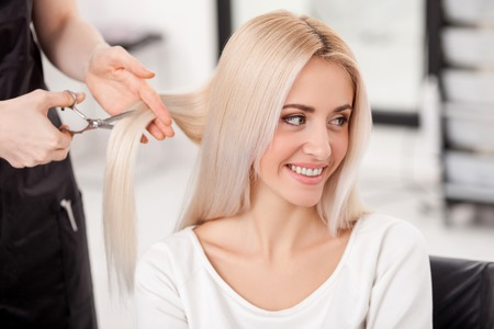 Photo pour Close up of hands of skillful hairstylist cutting female hair with scissors. The blond woman is smiling and looking aside with joy. She is sitting at hairdressing salon - image libre de droit
