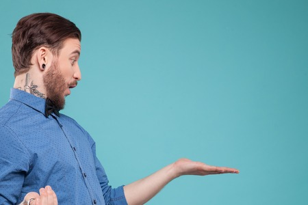 Photo for Handsome young bearded hipster is showing something with surprise. He is standing and raising arm sideways. Isolated and copy space in right side - Royalty Free Image