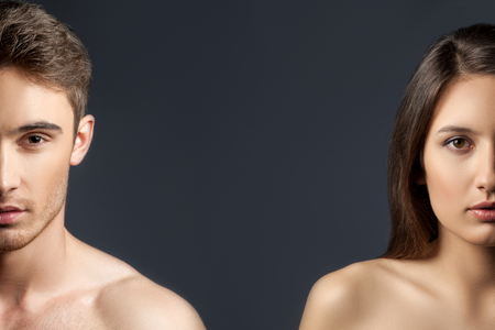 Foto de Portrait of half face of attractive young man and woman showing their perfect body and smooth skin. Isolated on black background - Imagen libre de derechos